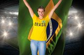 Excited football fan in brasil tshirt holding brasil flag against large football stadium with fans i