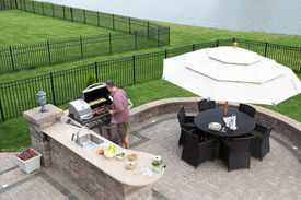 image of braai  - High angle view of a man cooking meat on a gas BBQ standing in the sunshine on a paved outdoor patio at the summer kitchen preparing for guests with a table and chairs with a garden umbrella alongside - JPG