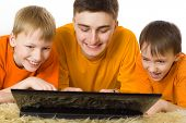 Three Brothers Looking At Laptop