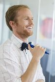 Happy businessman looking away while holding felt tip pen at creative office