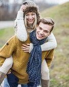Portrait of happy man piggybacking woman in park