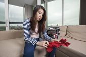 Young woman doing laundry work in living room at home