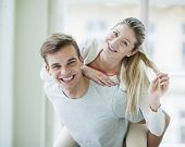 Portrait of happy young man giving piggyback ride to woman at home