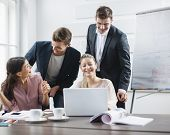 Successful young business people using laptop at desk in office