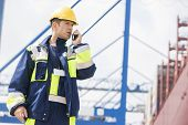 Mid adult male worker using walkie-talkie in shipping yard