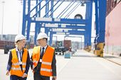 Engineers conversing while walking in shipping yard