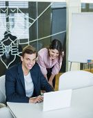 Portrait of smiling young businessman with female colleague using laptop at table in office