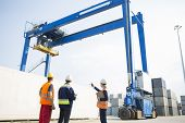 Workers discussing against large crane loading container at shipping yard
