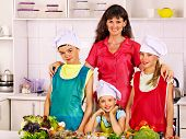 Happy mother and children cooking at kitchen.