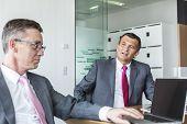 Mature businessmen discussing in office