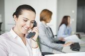 Smiling young businesswoman using landline telephone with colleagues in background at office