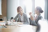 picture of lunch  - Smiling young businesswomen having lunch at table in office - JPG