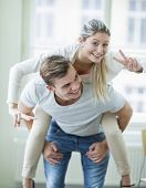 Portrait of happy woman enjoying piggyback ride given by man at home