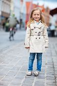 Portrait of adorable little girl outdoors in city on autumn or spring day
