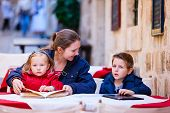 Young mother and her two kids at outdoor cafe on autumn or spring day