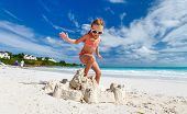 Little girl at tropical beach jumping on a sand castle having fun