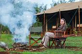 Safari vacation. Woman enjoying evening sitting by campfire.