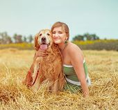 happy young woman with her dog golden retriever in rural areas in summer