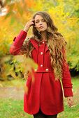 Young fashion woman with long hair dressed in red coat posing in autumn park.