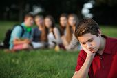 stock photo of depressed teen  - Sulking male caucasian teen with face in hands - JPG