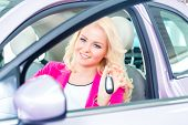 Woman buying new car at dealership showing key