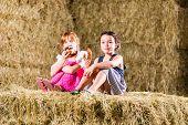 Bavarian girls sitting on hayloft with pretzels