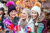 stock photo of christmas spices  - Woman drinking mulled wine in mug on German Christmas Market - JPG