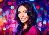Portrait of beautiful brunette looking at camera with toothy smile over sparkling background