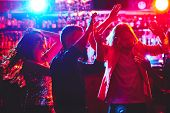 Group of young people with raised arms dancing in nightclub