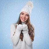 Winter. Cute girl during snowfall