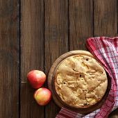 Closeup photo of holiday apple pie on rustic wooden background, top view point, square composition