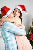 Young happy couple hugging near New Year`s tree
