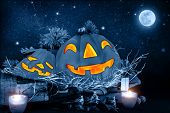 Halloween night, scary carved pumpkin head glowing in dark starry night, full moon, traditional october holiday, horror concept
