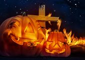 Creepy Halloween night, glowing carved pumpkin with scary horrible spiders, cross and burning flame on the graveyard in mysterious dark night