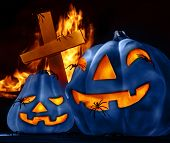 Closeup on scary Halloween decorations, eerie glowing blue carved pumpkin, cross and burning fire on graveyard, uncanny holiday night