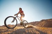 Man cycling in the desert with lot of dust