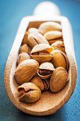 salt pistachios in a wooden spoon