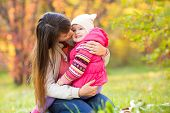 beautiful mother with kid girl outdoors in autumn