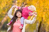 beautiful woman with kid girl outdoor in autumnal park