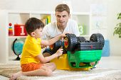 child boy and his father repair toy car