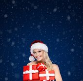 Beautiful lady in Christmas cap holds a set of gifts wrapped with red paper,winter background