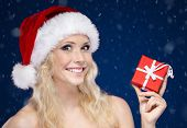 Pretty woman in Christmas cap hands present wrapped with red paper, on blue snow background