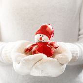 Female hands holding a cute happy Snowman. Woman hands in teal mittens showing a Snowman gift dresses in red hat and scarf. Cute Christmas present. Winter holidays concept.