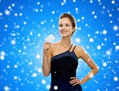 shopping, wealth, holidays and people concept - smiling woman in evening dress holding credit card over blue snowy background