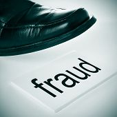a man foot wearing a black shoe stepping in a signboard with the word fraud written in it
