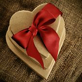 a pile of heart-shaped gift boxes with a red ribbon bow, with a retro effect