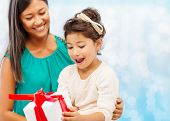 christmas, holidays, celebration, family and people concept - happy mother and girl with gift box over blue lights background
