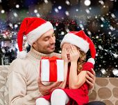 family, christmas, winter holidays and people concept - smiling daughter with closed eyes waiting for present from father over snowy night city background
