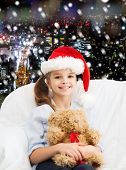holidays, presents, christmas, childhood and people concept - smiling little girl with teddy bear toy over snowy night city background