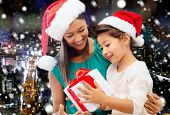 christmas, holidays, celebration, family and people concept - happy mother and little girl in santa helper hats with gift box over snowy night city background